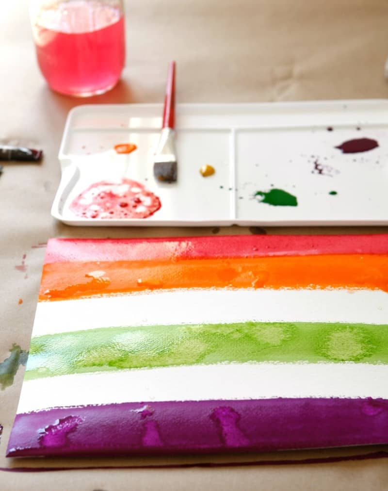 Watercolor painting stripes for a rainbow weaving art project for kids