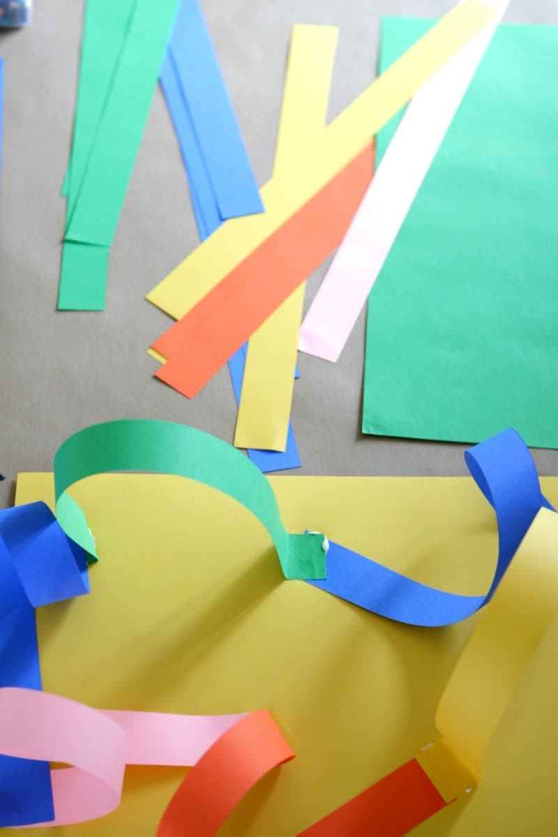 Cutting paper strips for a roller coaster paper art project for kids