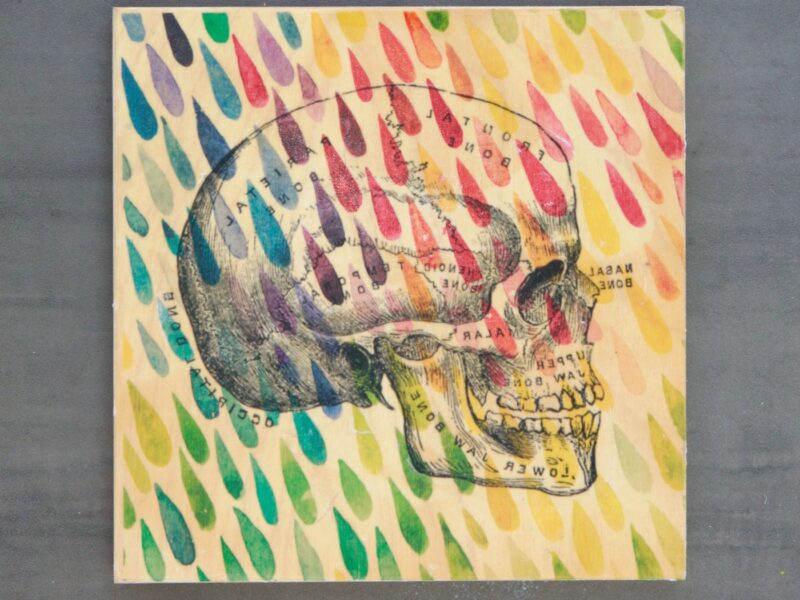 square piece of wood with skull illustration and colorful raindrops image transferred onto it