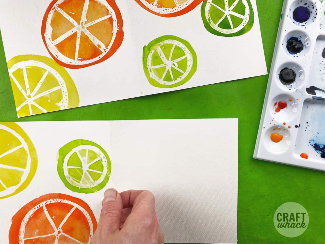 masking fluid being peeled from a fruit slice watercolor card